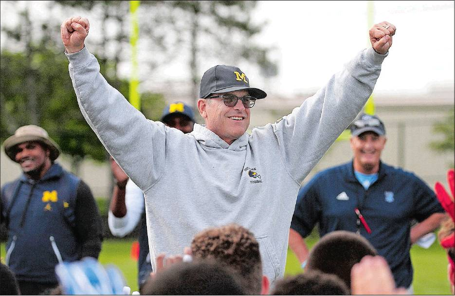 quality design 63d1c 82df0 Michigan coach Jim Harbaugh finishes off a talk to high school players and  potential recruits with a cheer as URI coach Jim Fleming, right, looks on  during ...